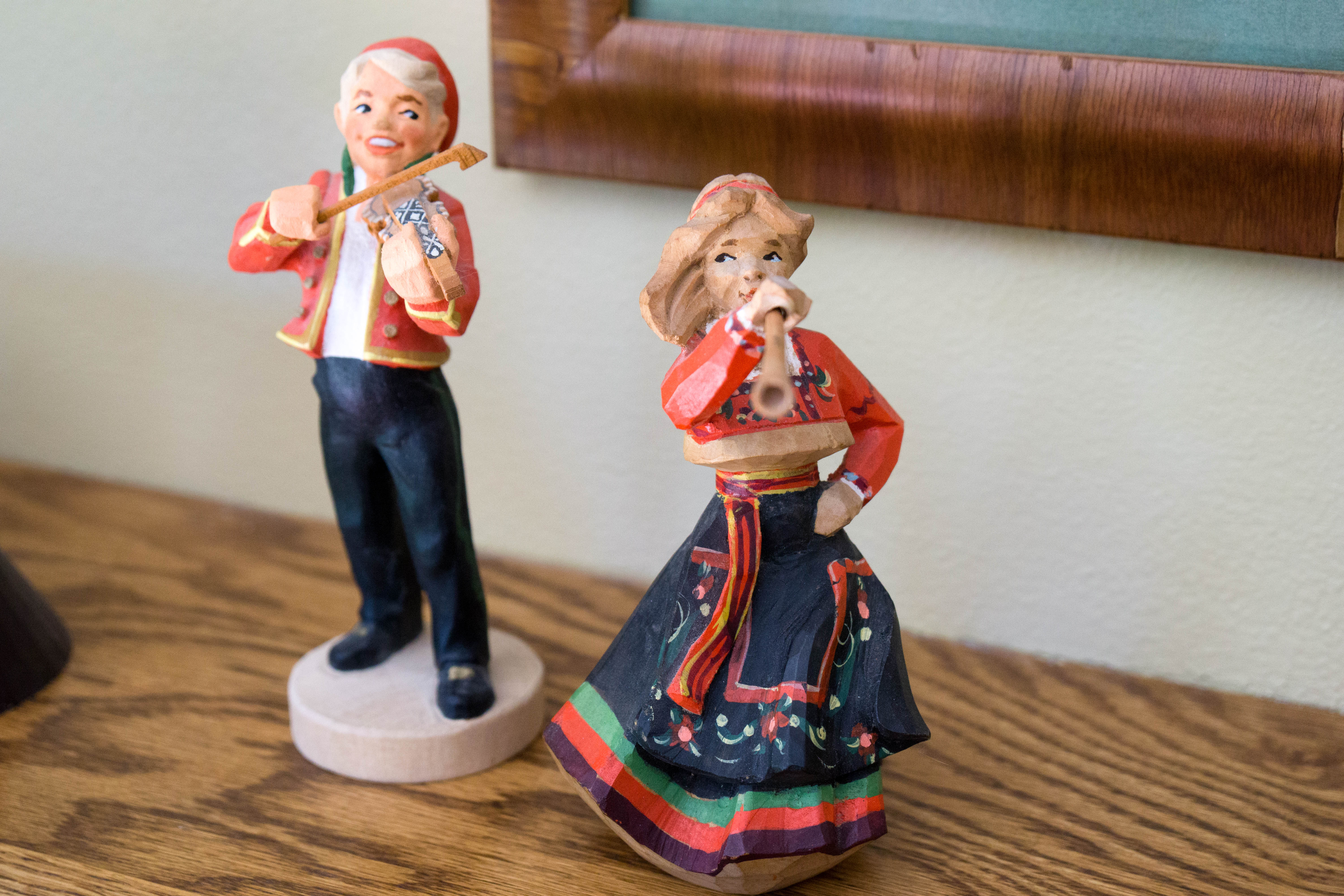Two carved wooden figurines depicting musicians in Norwegian folk costumes.